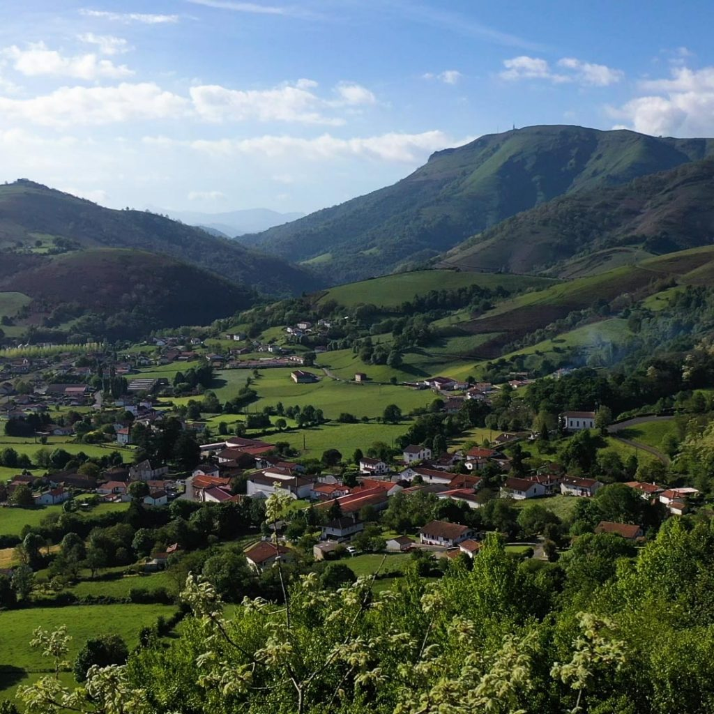 Landscape of green hills with village in the valley