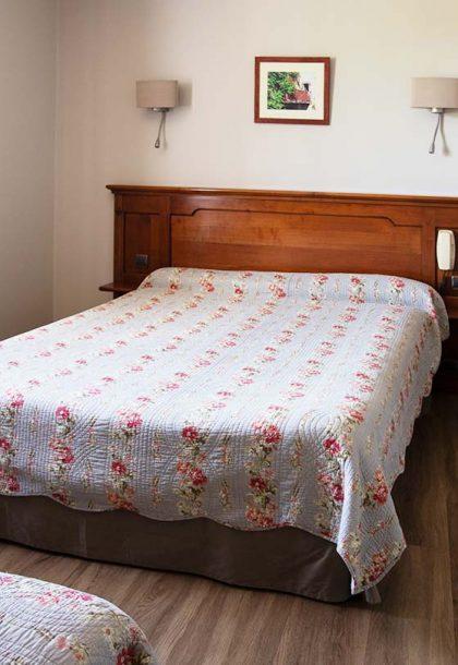 Queen bed in beige hotel room